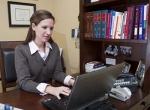 woman working at a desk - KM Family Law