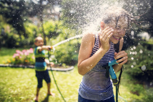 Little boy is splashing his sister with garden hose. on a sunny summer day. - KM Family Law