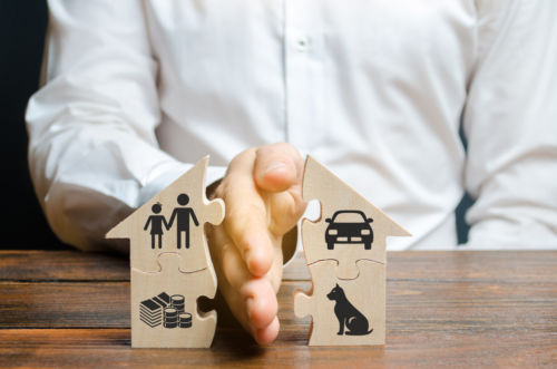 A man splits a house with his palm with images of property, children and pets. - KM Family Law